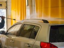 Le travailleur de station de lavage lave une voiture Photos stock