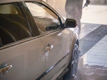 Le travailleur de station de lavage lave une voiture Images stock