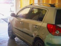 Le travailleur de station de lavage lave une voiture Images libres de droits