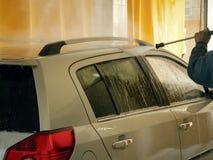 Le travailleur de station de lavage lave une voiture Photographie stock libre de droits