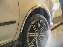 Le travailleur de station de lavage lave une voiture Image libre de droits