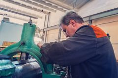 Le travailleur de Turner contrôle le processus métallurgique de la coupe mécanique sur un tour image stock