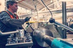 Le travailleur de Turner contrôle le processus métallurgique de la coupe mécanique sur un tour photo stock