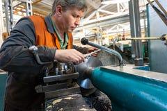 Le travailleur de Turner contrôle le processus métallurgique de la coupe mécanique sur un tour photos stock