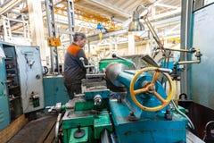 Le travailleur de Turner contrôle le processus métallurgique de la coupe mécanique sur un tour image libre de droits