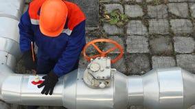 Le travailleur dessine la flèche près de la valve Timelapse banque de vidéos