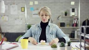 Le travailleur discipliné blond de bureau souffle un sifflement de penny, utilisant un chapeau d'anniversaire Concept étant ennuy banque de vidéos