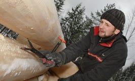 Le travailleur du bois utilise l'outil de mesure pendant le blockhaus de bâtiment dans la victoire images stock