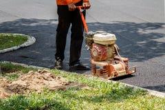 Le travailleur emploie l'asphalte de compactage de compacteur vibratoire de plat à la réparation de route photo stock