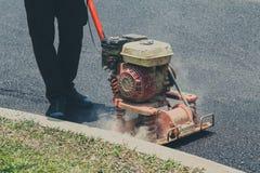 Le travailleur emploie l'asphalte de compactage de compacteur vibratoire de plat photo libre de droits