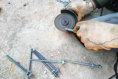 Le travailleur emploie une broyeur d'angle pour affiler les boulons, un plan en gros plan photos stock