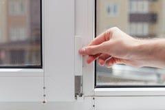 Le travailleur enlève la prise protectrice de l'élément de la fenêtre en plastique Préparer une fenêtre en plastique pour des rép image libre de droits