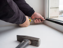 Le travailleur enlève le verre isolant de serrure d'une fenêtre en plastique photos stock