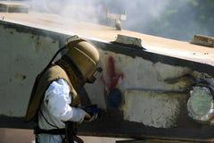 Le travailleur est enlèvent la peinture par le soufflage de sable de pression atmosphérique Photographie stock