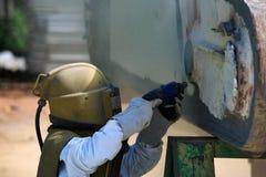 Le travailleur est enlèvent la peinture par le soufflage de sable de pression atmosphérique Photo libre de droits