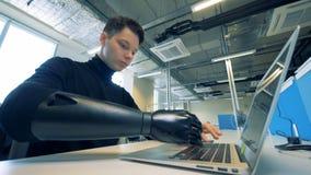 Le travailleur handicapé utilise sa prothèse au bureau 4K clips vidéos