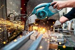 Le travailleur industriel à l'aide d'une mitre composée a vu avec la lame circulaire Photos libres de droits