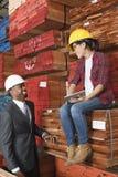 Le travailleur industriel et le mâle féminins machinent le sourire tout en regardant l'un l'autre à la cour de bois de constructio Photo libre de droits