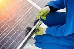 Le travailleur installe les batteries solaires utilisant des outils par temps couvert de neige Image libre de droits