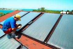 Le travailleur installe les panneaux solaires Photo stock