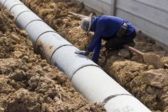 Le travailleur installent des trous d'homme de béton préfabriqué image libre de droits