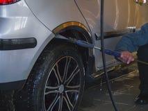 Le travailleur lave la roue d'une voiture Photographie stock