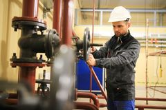 Le travailleur mécanique ferme la soupape à vanne de la canalisation dans l'usine industrielle de gas et de pétrole image libre de droits