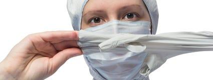 Le travailleur médical enlève un gant en caoutchouc de sa main image stock