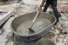 Le travailleur mélange le ciment photos stock