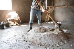 Le travailleur mélange le mortier images libres de droits