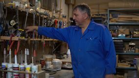 Le travailleur mûr choisit des outils dans l'atelier Homme sur le fond des accessoires fonctionnants clips vidéos