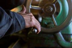 Le travailleur manoeuvrent la vieille machine sur l'usine Photos libres de droits