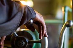 Le travailleur manoeuvrent la vieille machine sur l'usine Image libre de droits