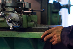 Le travailleur manoeuvrent la vieille machine sur l'usine Photos stock