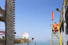 Le travailleur marchant vers le haut des escaliers à mettent sur cric l'installation de pétrole et de gaz Photos libres de droits