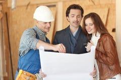 Le travailleur montre des plans de développement de maison photographie stock libre de droits