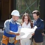 Le travailleur montre des plans de développement de maison photo libre de droits