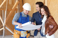 Le travailleur montre des plans de développement de maison photographie stock