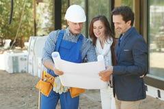 Le travailleur montre des plans de développement de maison images stock