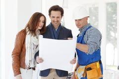 Le travailleur montre des plans de développement de maison image libre de droits