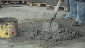 Le travailleur pellant mélangeant un béton et le met dans le seau au chantier de construction banque de vidéos