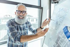 Le travailleur plus âgé agréable joyeux est tableau de conférence proche debout Photos libres de droits