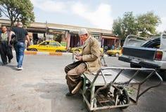 Le travailleur plus âgé compte l'argent gagné pendant un jour approximatif Photo libre de droits