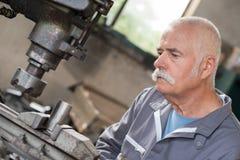 Le travailleur plus âgé observe traiter le détail sur la fraiseuse photo libre de droits
