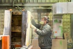 Le travailleur polit la couche d'amorce Travaillez à la préparation du lit de machine pour la peinture suivante Photo libre de droits