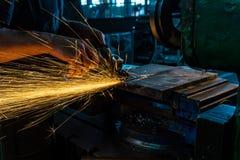 Le travailleur polit le métal avec une machine de meulage et étincelle le plan rapproché images libres de droits