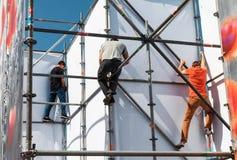 Le travailleur prépare le panneau d'affichage à installer la nouvelle publicité photos stock