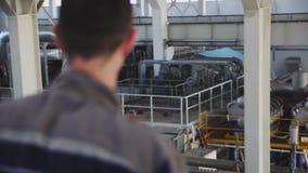 Le travailleur qualifié regarde le réseau de pipe-lines dans l'atelier d'usine clips vidéos