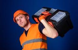Le travailleur, réparateur, dépanneur, constructeur fort sur le visage réfléchi porte la boîte à outils sur l'épaule, préparent p Photos stock