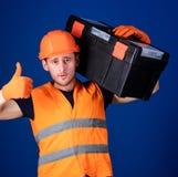 Le travailleur, réparateur, le dépanneur, constructeur sur le visage sûr porte la boîte à outils sur l'épaule Homme dans le casqu Photos libres de droits